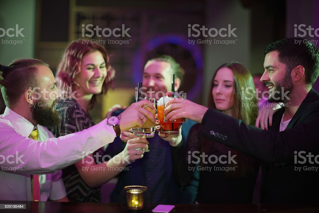 Friends toasting with drinks in bar stock photo