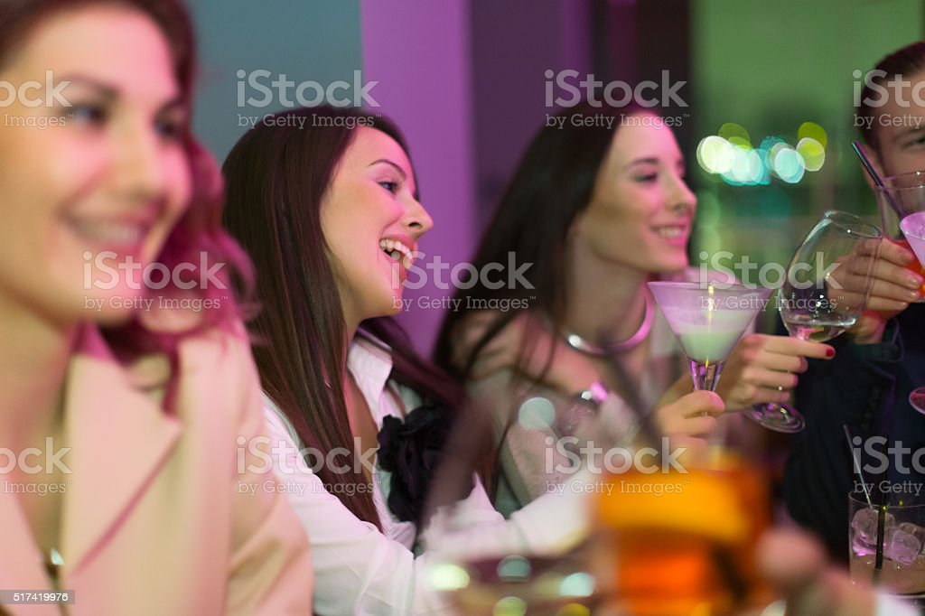 Friends toasting with drinks in nightclub stock photo