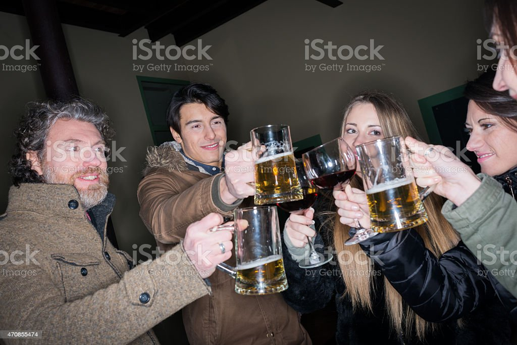 Friends toasting with wine and beer outside pub at night stock photo