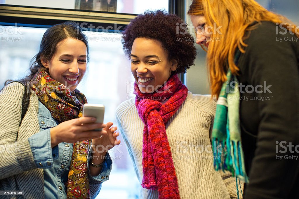 Friends traveling by train using mobile phone stock photo
