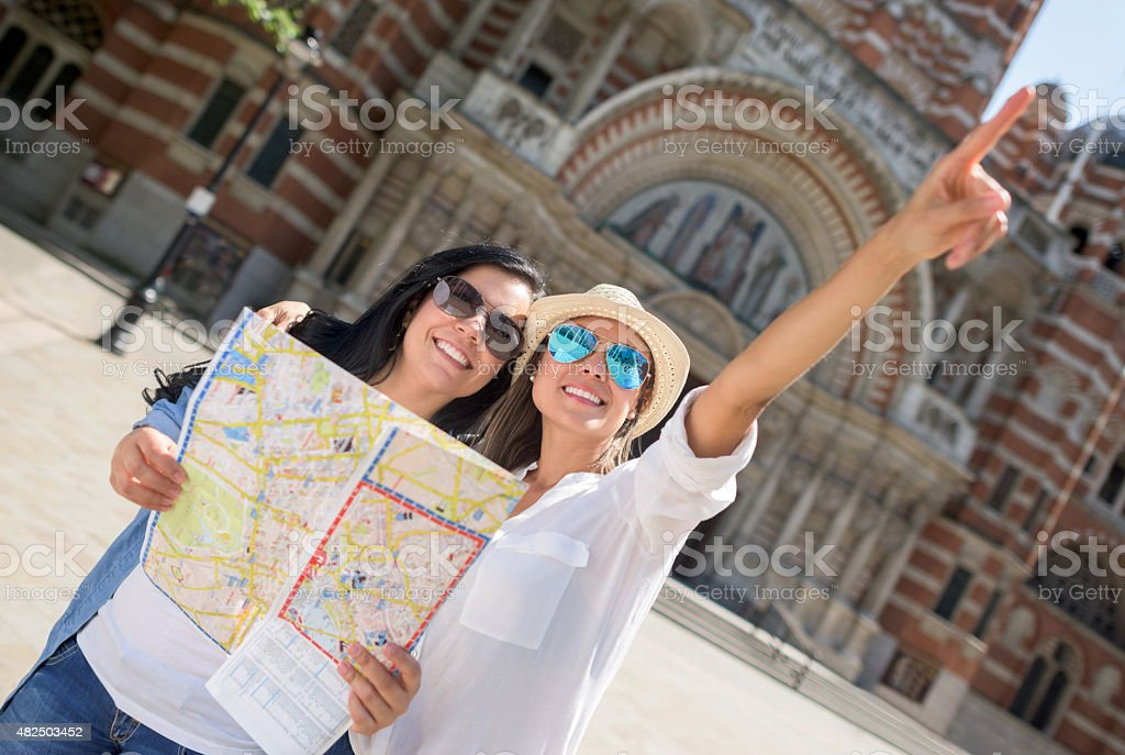 Friends traveling together and holding a map stock photo