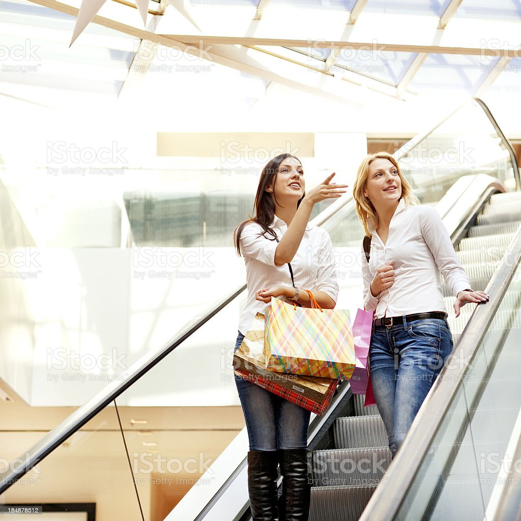 Friends, two women taking escalator in shopping mall royalty-free stock photo