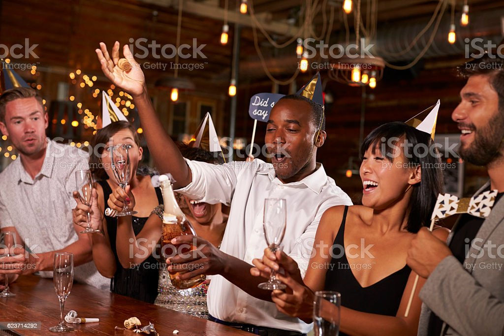 Friends uncorking champagne at a New Year's party at a bar stock photo
