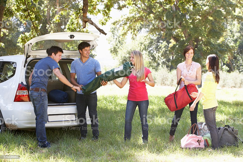 Friends Unloading Camping Equipment From Car stock photo