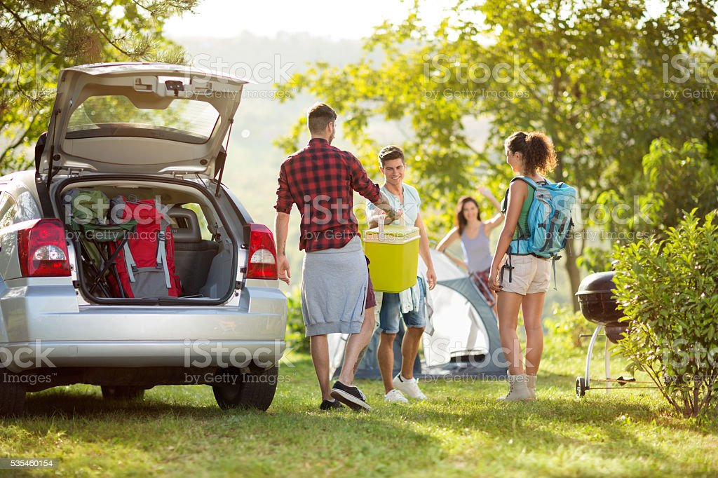 friends unpacking car for camping stock photo