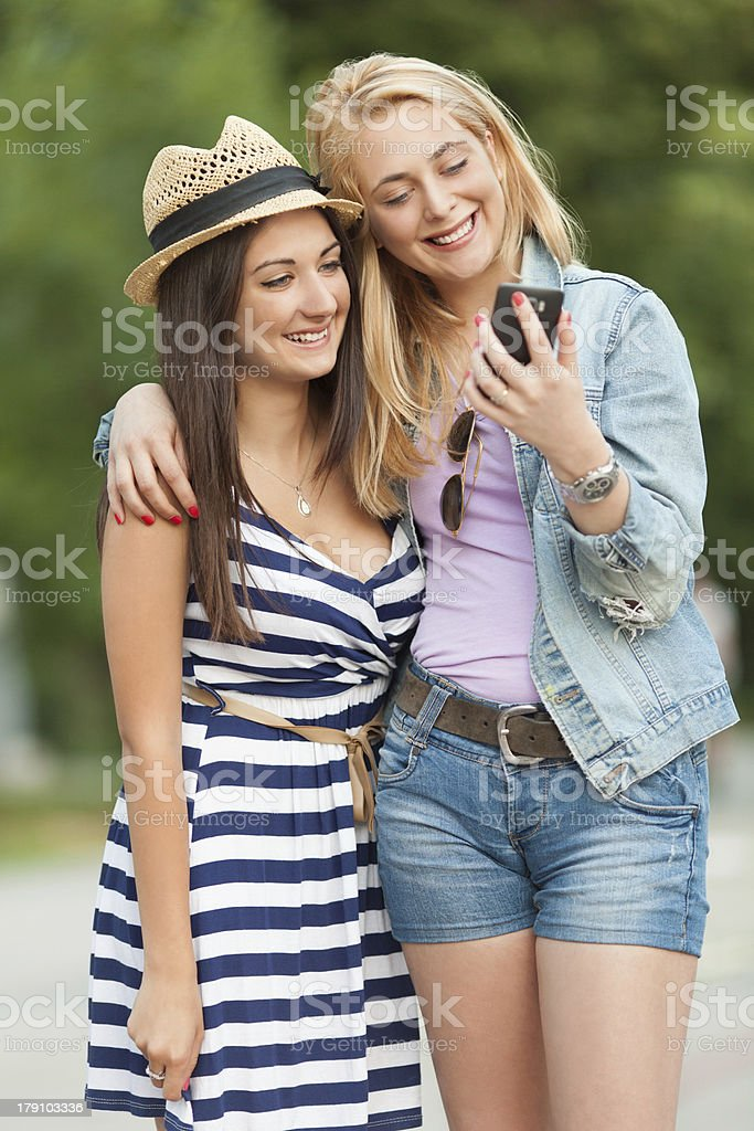 Friends using a smart phone royalty-free stock photo