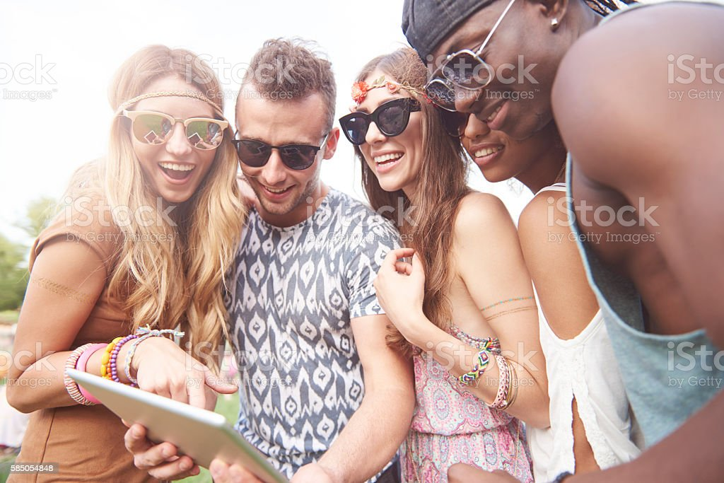 Friends using digital tablet at the music festival stock photo