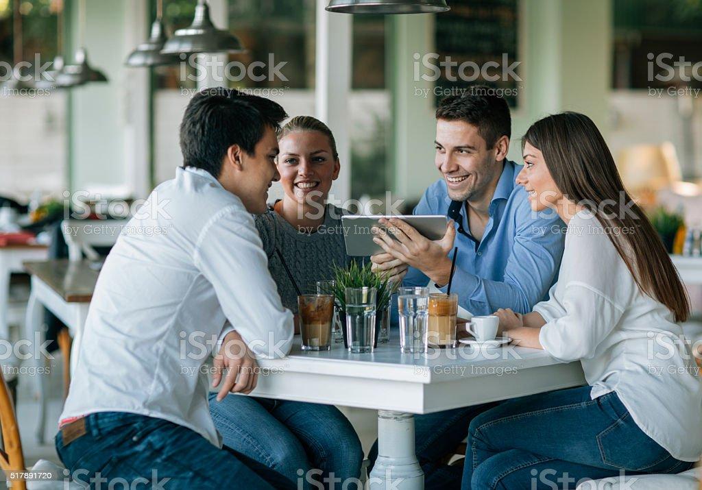Friends Using Digital Tablet In Restaurant stock photo