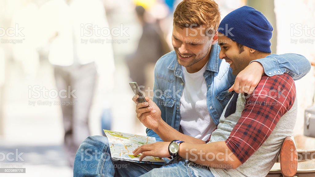 Friends using map during city trip stock photo