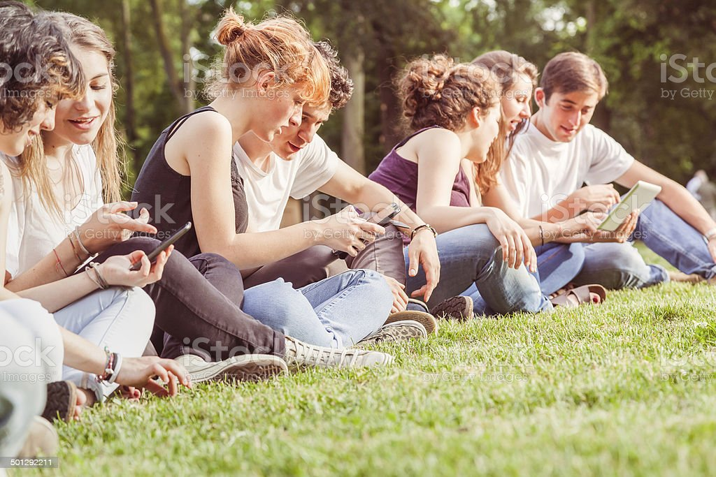 Friends Using Mobile Devices Outdoor At Sunset stock photo