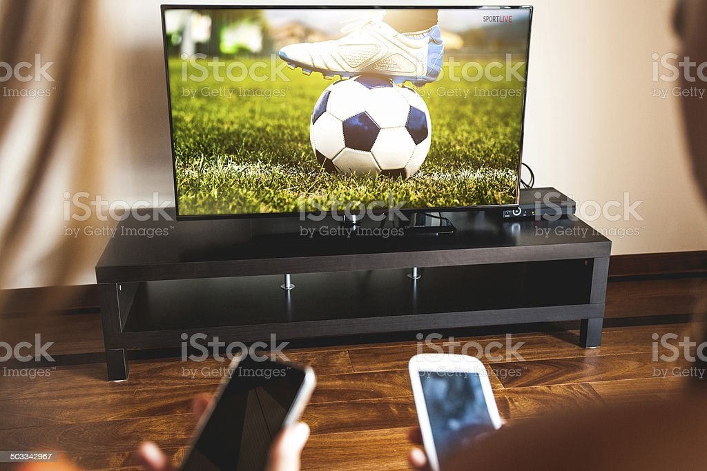 Friends using mobile phone during a soccer match stock photo