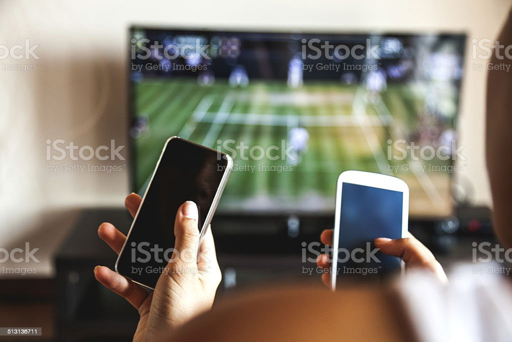Friends using mobile phone during a tennis match stock photo
