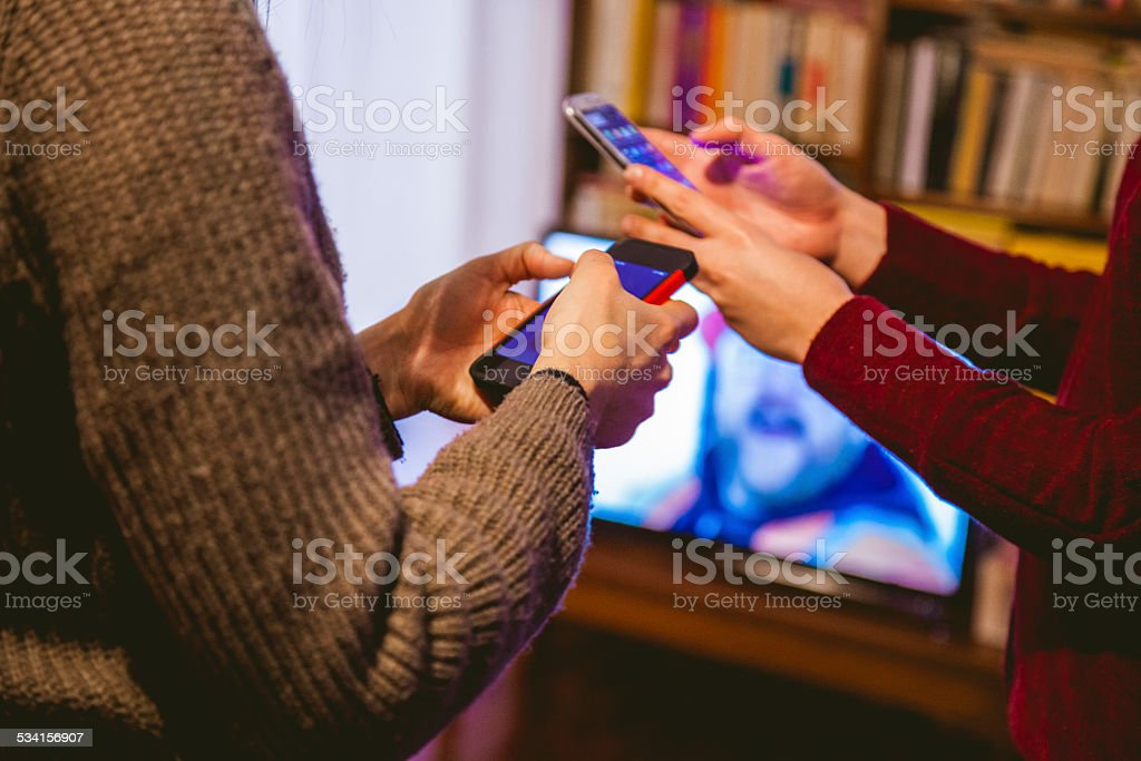 Friends using mobile phone while whatching TV stock photo