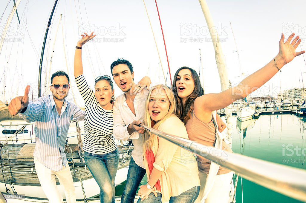 Friends using selfie stick taking pic on exclusive luxury sailboat stock photo