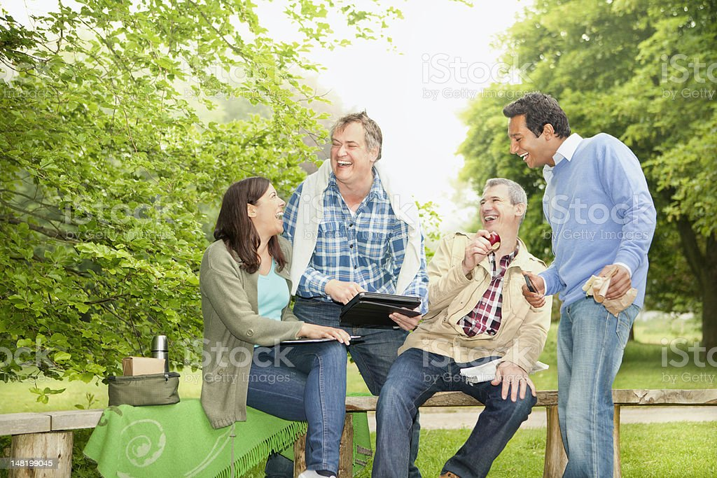 Friends using tablet computer in park stock photo
