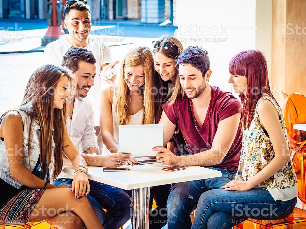 Friends Using Tablet Together At The Bar stock photo