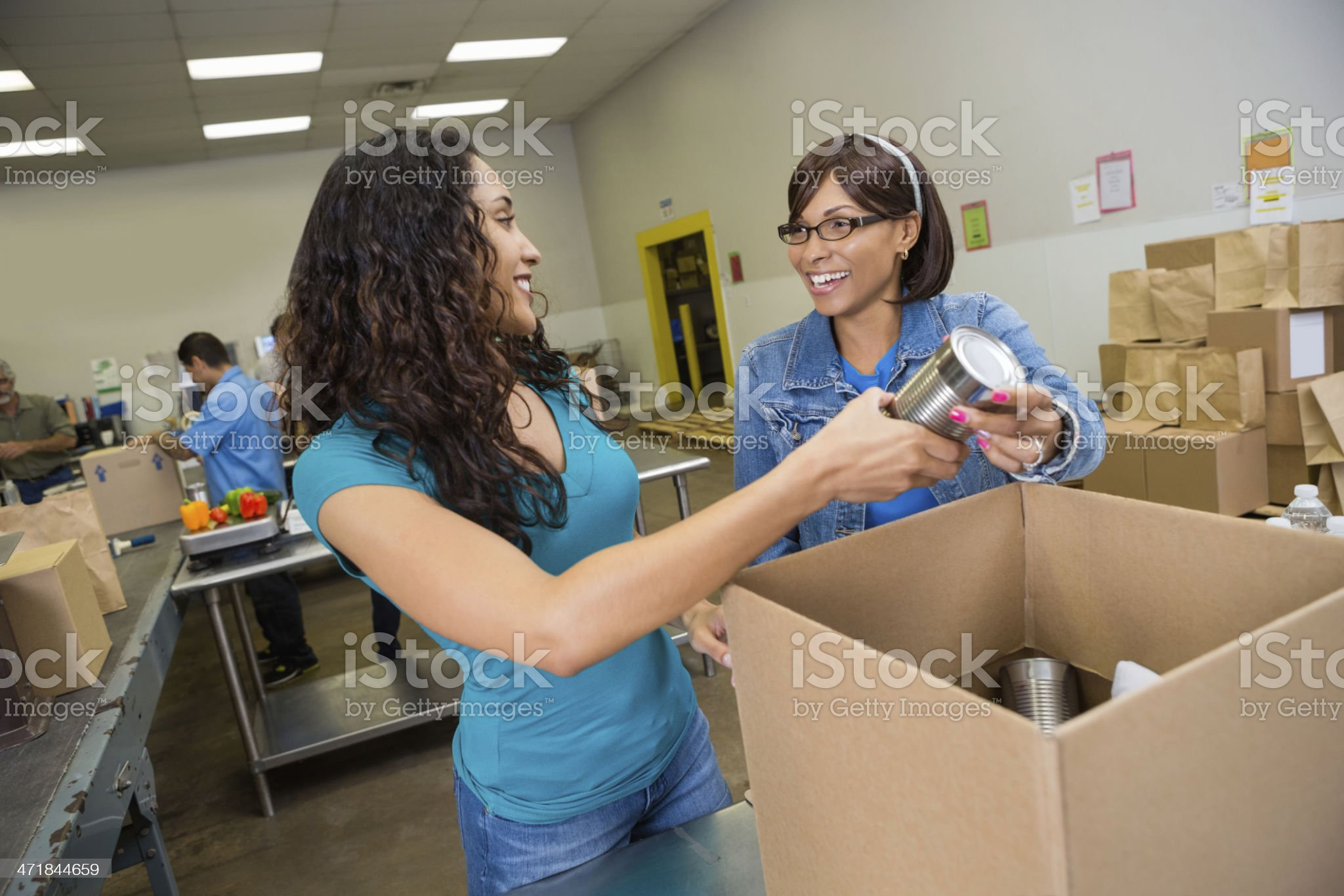 Friends volunteering to sort donation at food bank royalty-free stock photo