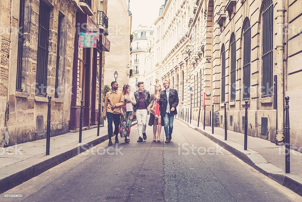 Friends walking along streets of Paris stock photo