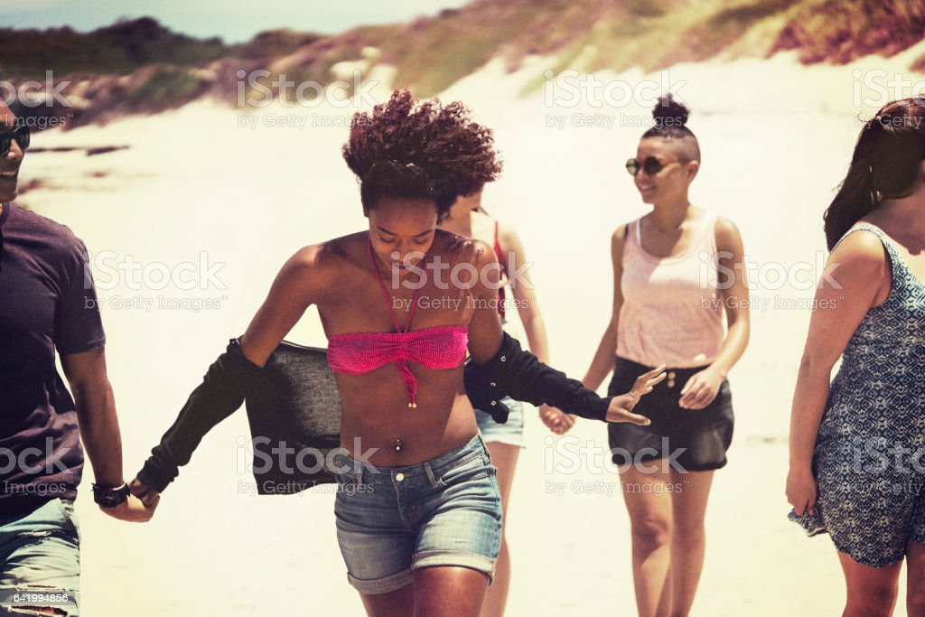 Friends walking at beach during summer stock photo