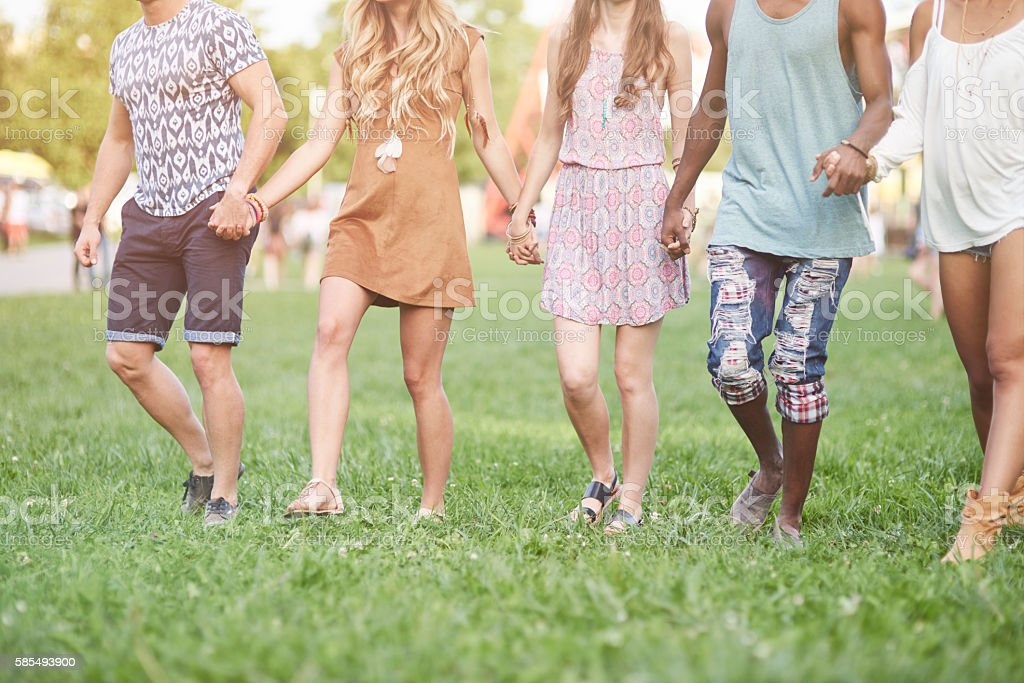 Friends walking hand by hand stock photo
