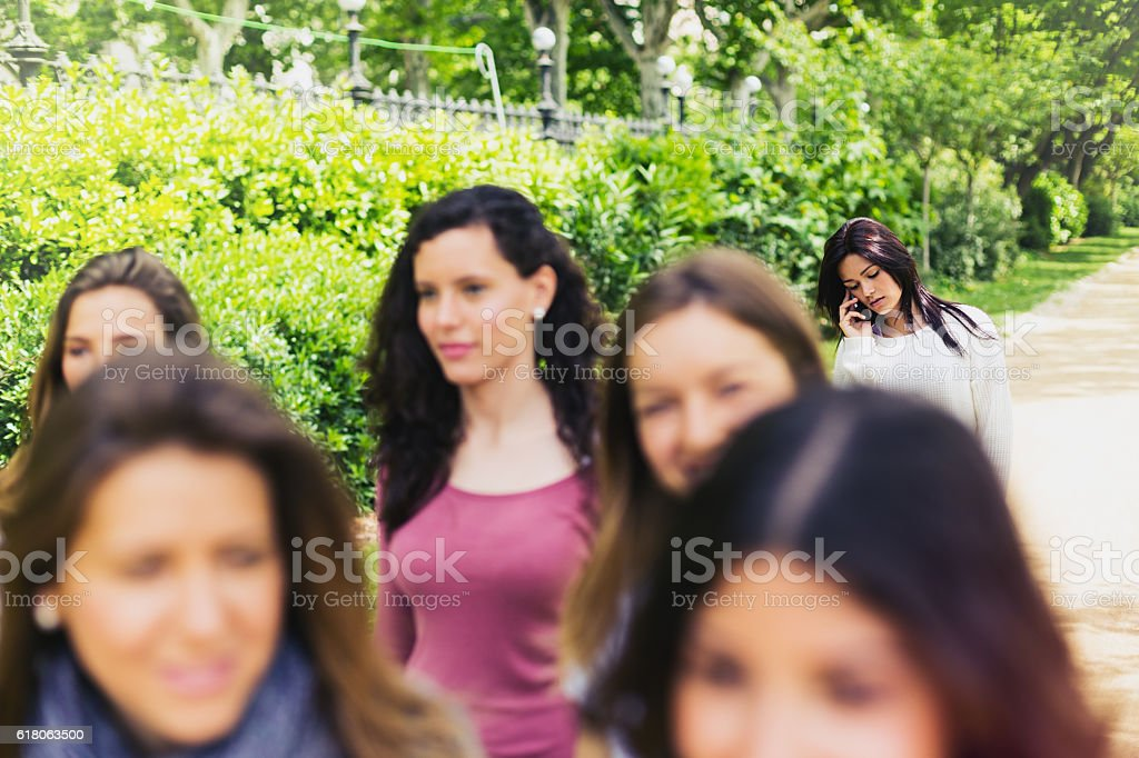 Friends walking in a park and talking on the phone. stock photo