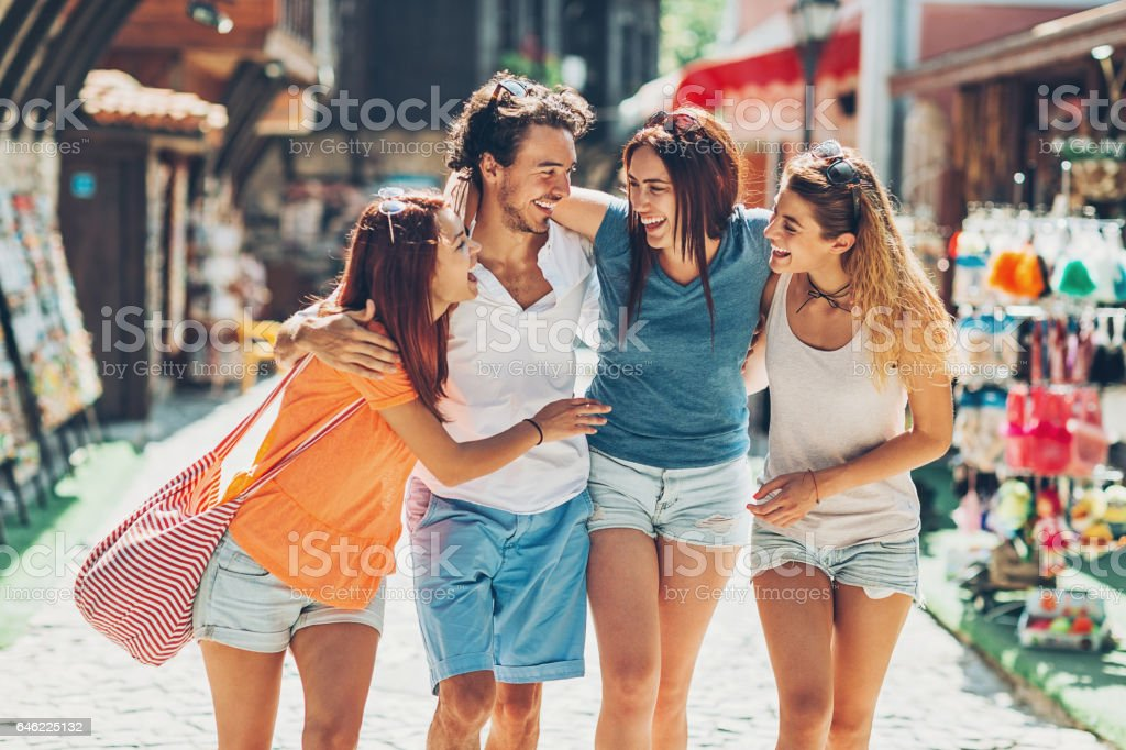 Friends walking on a shopping street and laughing stock photo