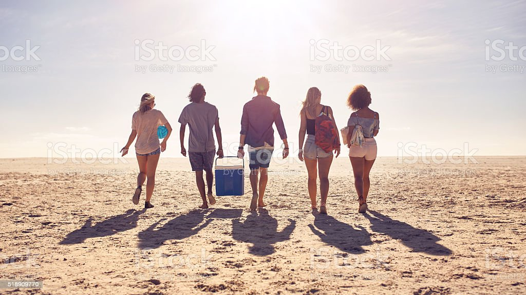 Friends walking on the beach carrying a cooler box stock photo