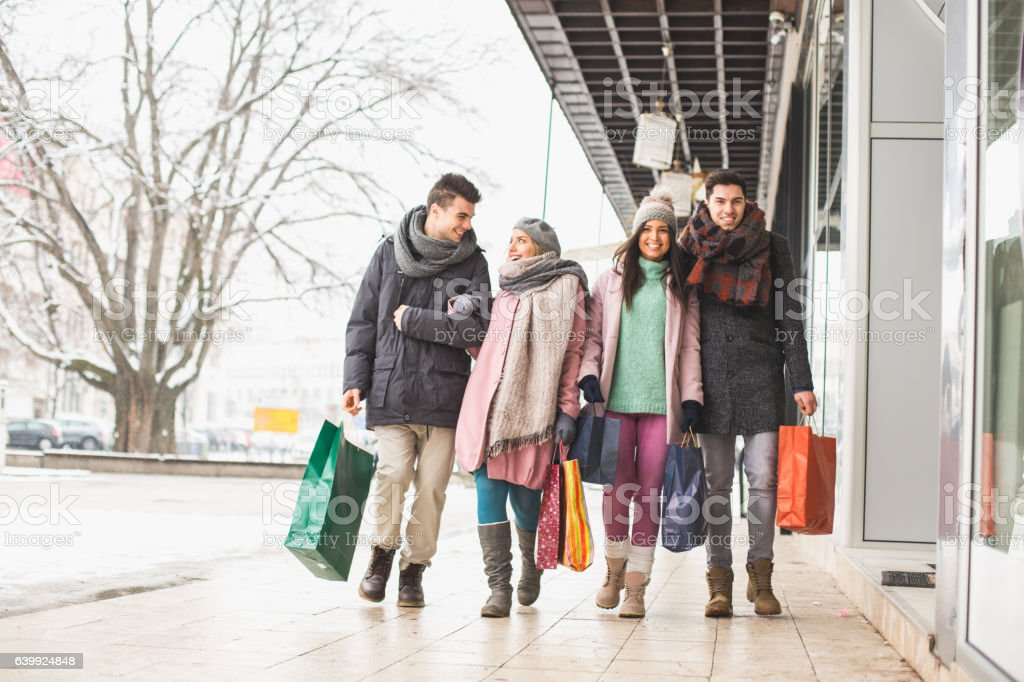 Friends walking on the street with shopping bags stock photo