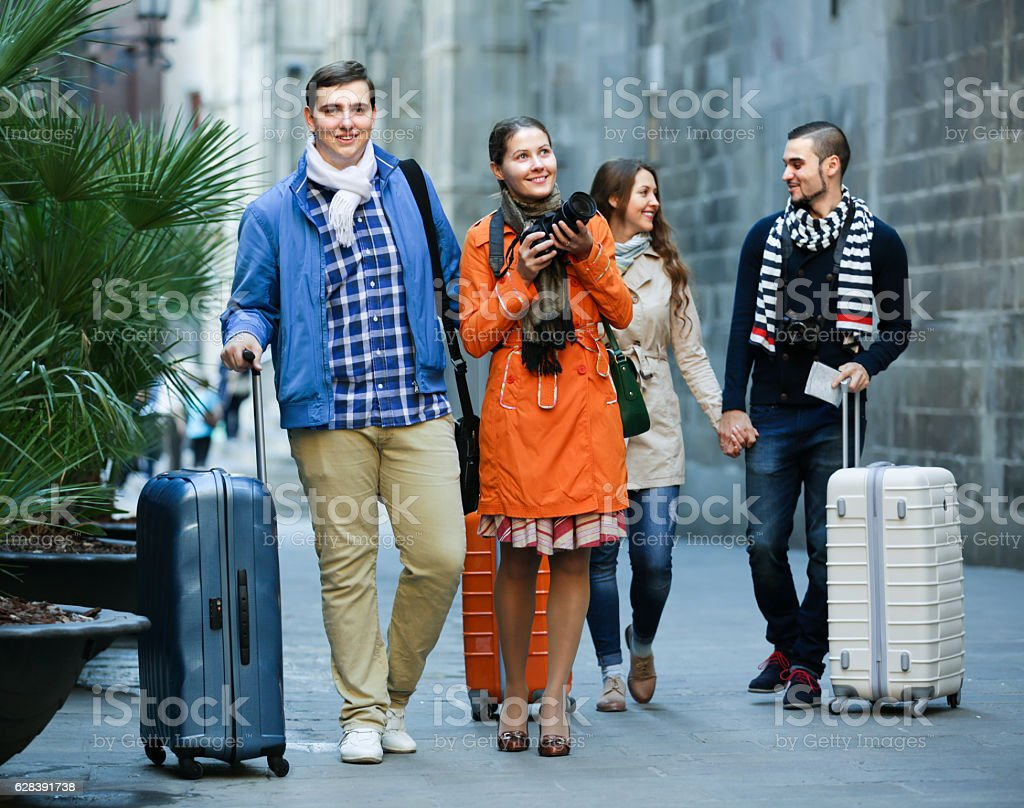 friends  walking through city street stock photo
