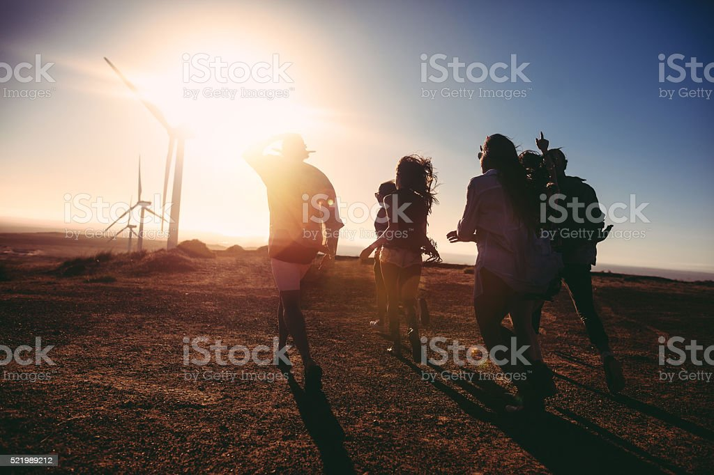 Friends walking towards vintage car at sunset in wind park stock photo
