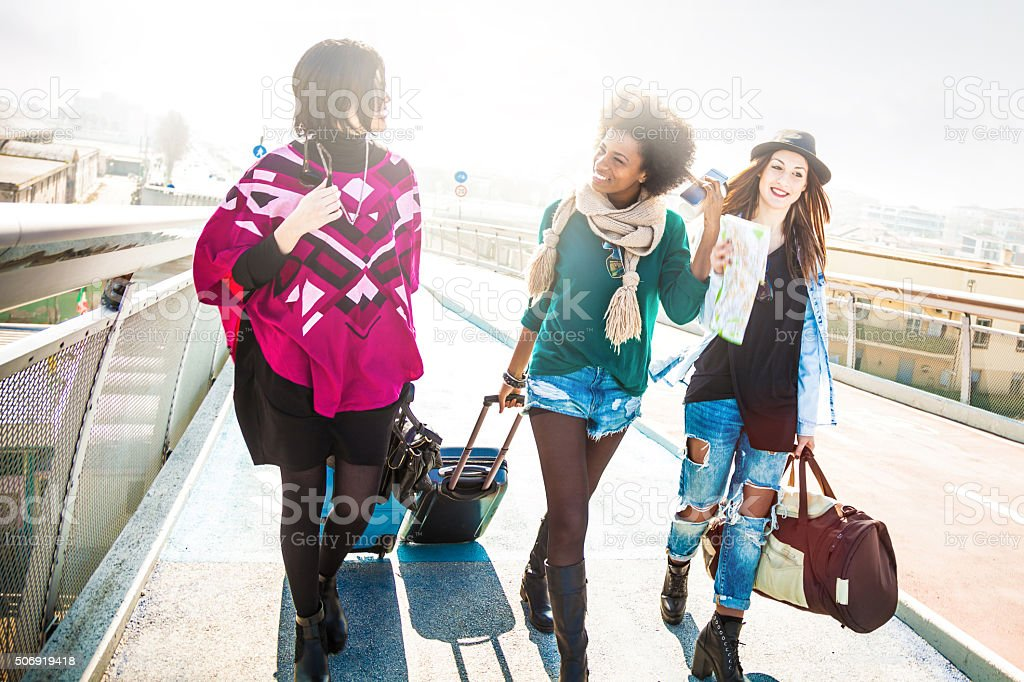Friends walking with luggages starting an awesome trip stock photo