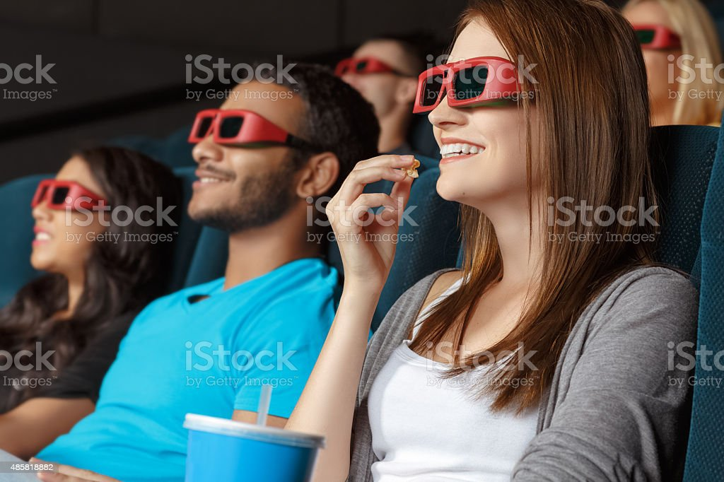 Friends watching 3D movie in the cinema stock photo