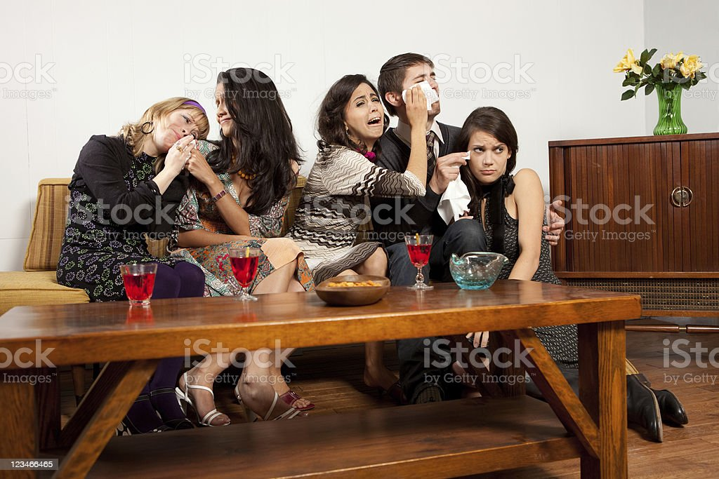 Friends watching a sad tv show stock photo