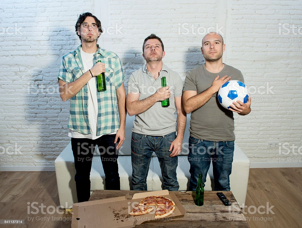 friends watching f television emulating football players listening national anthem stock photo