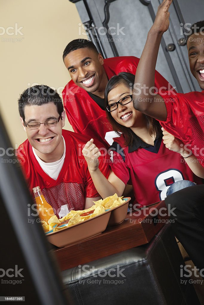 Friends watching football game on TV together royalty-free stock photo