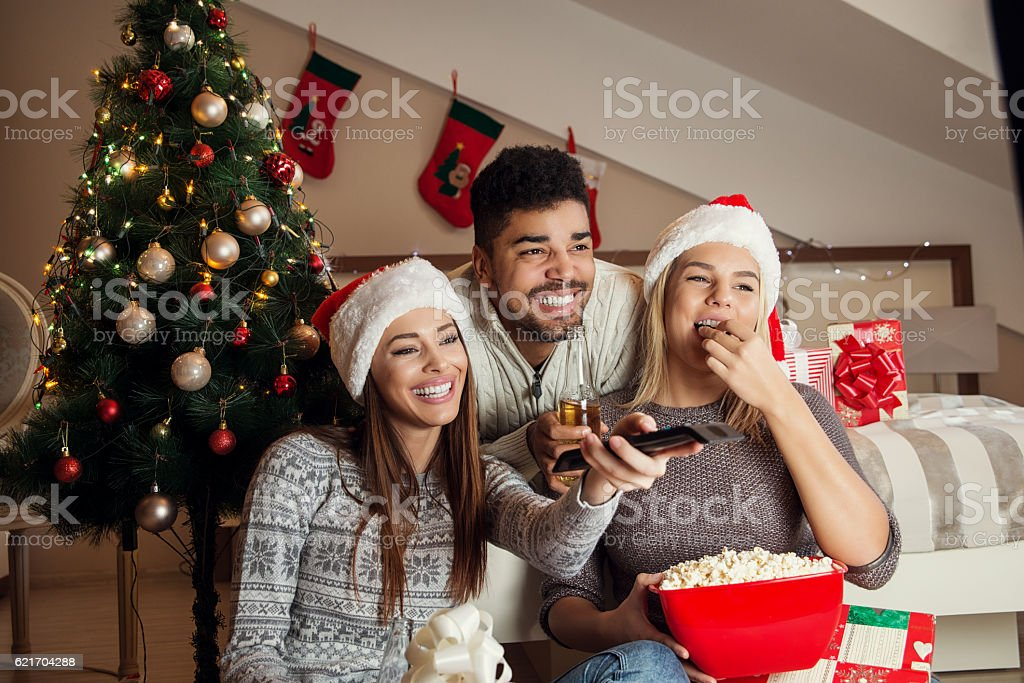 Friends watching movie and having fun at Christmas eve. stock photo