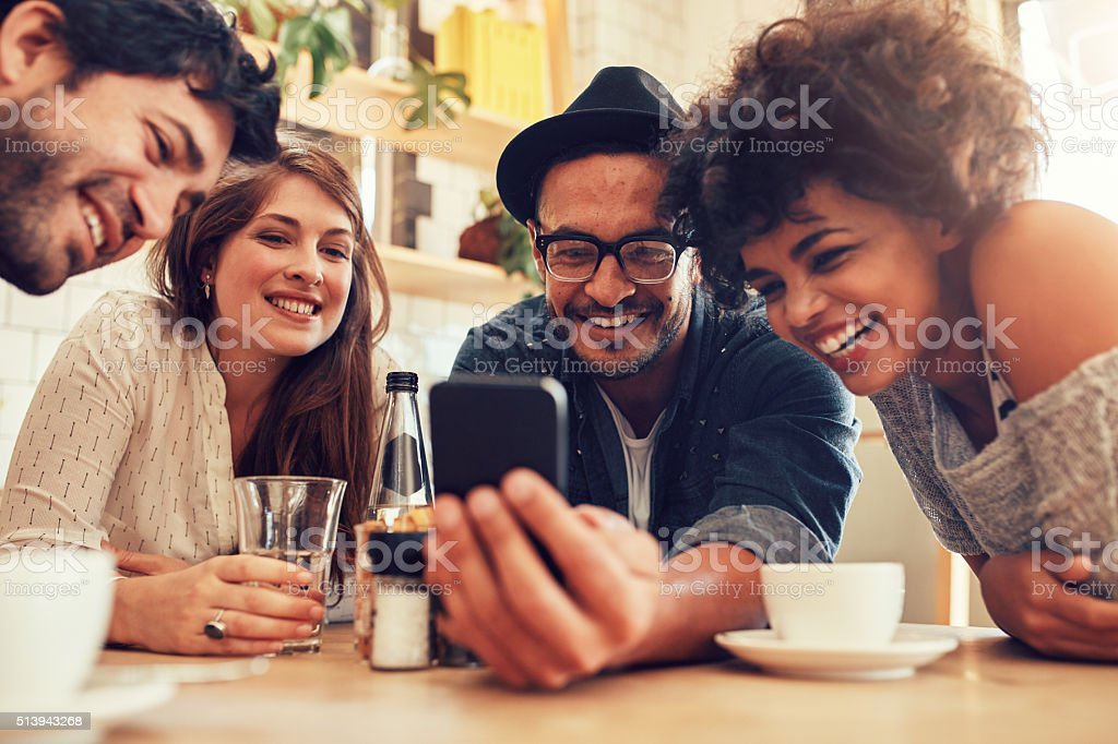 Friends watching photos on mobile phone stock photo