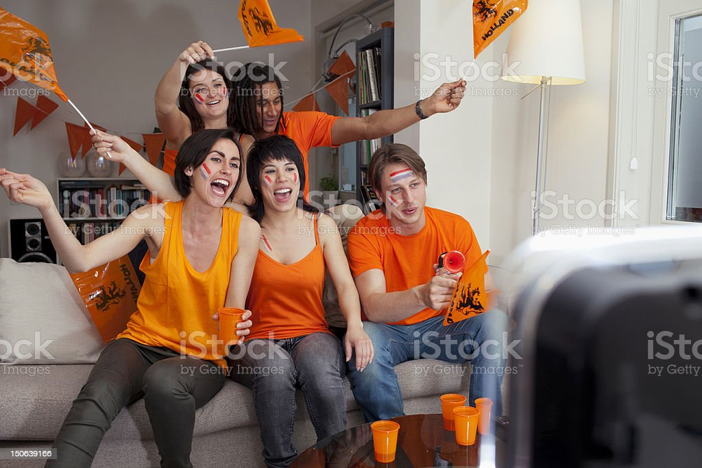 Friends watching sports on television stock photo