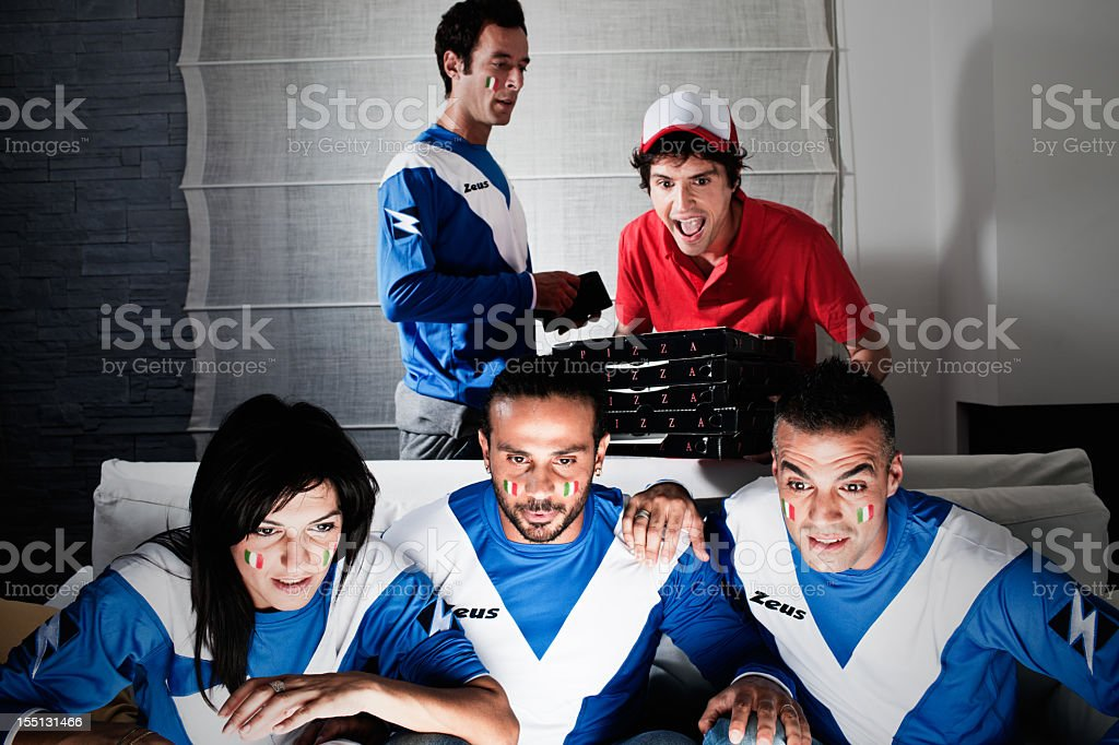 Friends watching sports tv with pizza delivery man stock photo