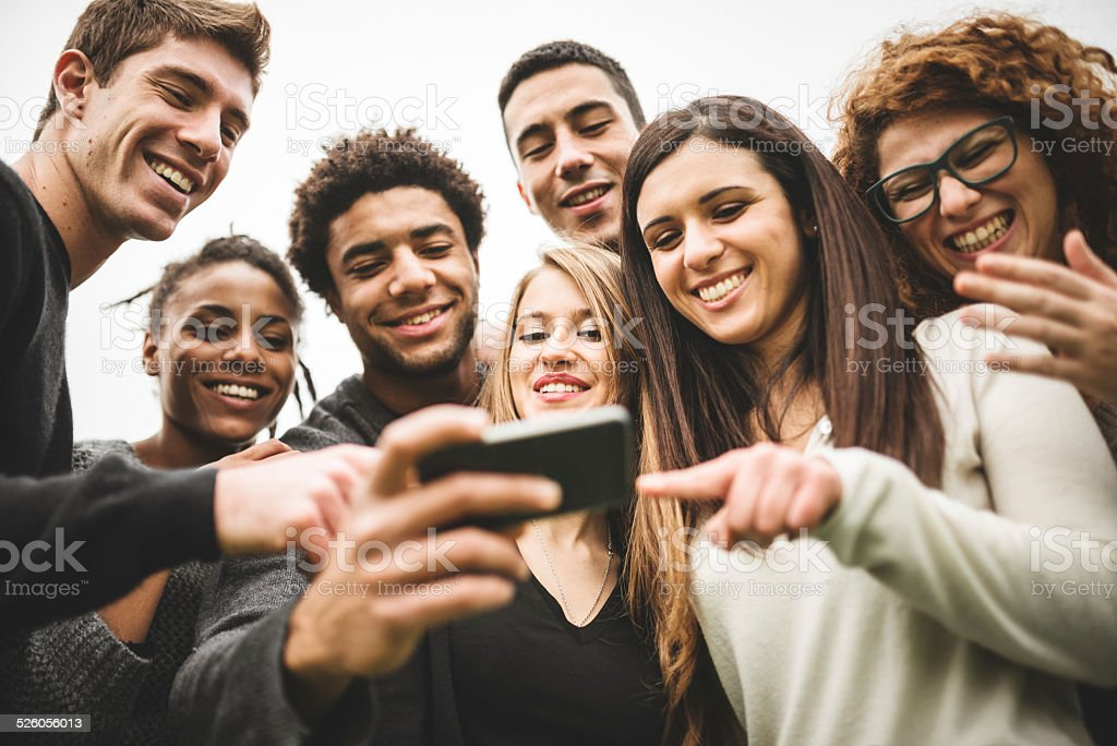 friends watching the selfies done on the phone stock photo
