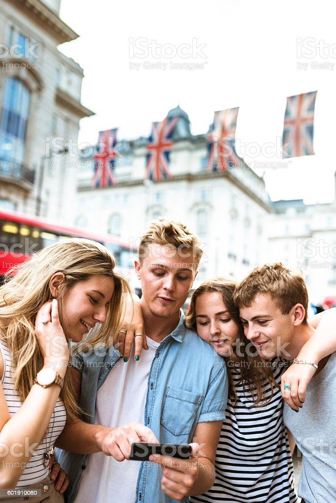friends watching the smartphone in piccadilly circus stock photo