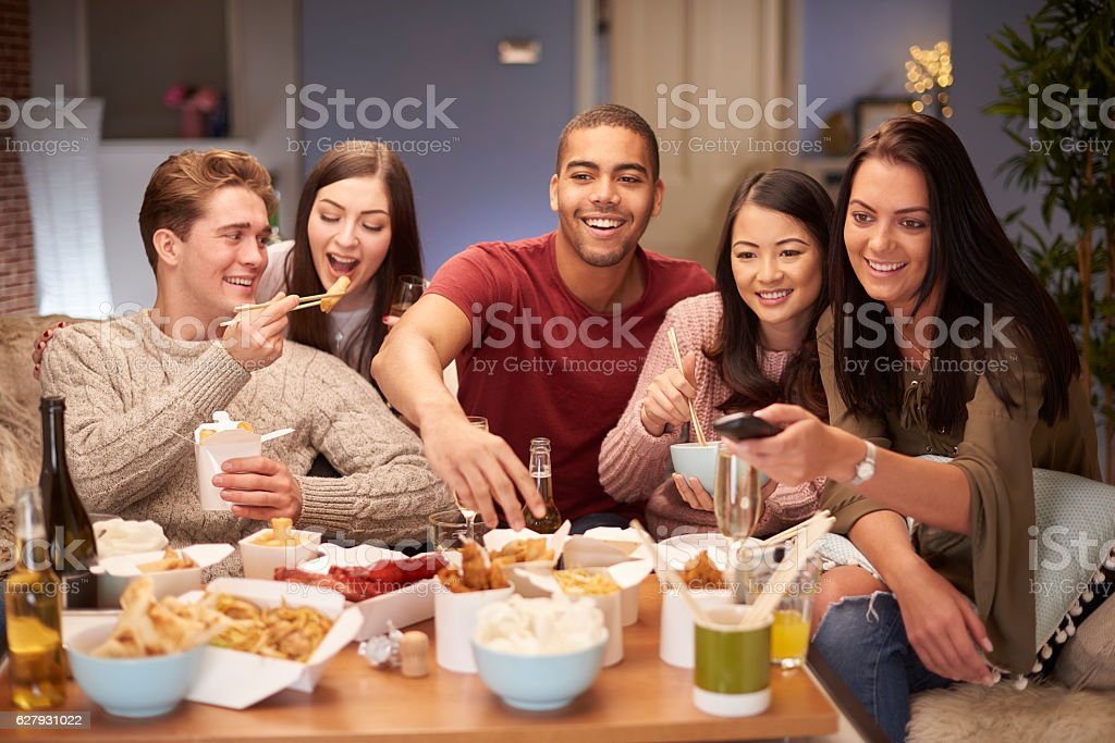friends watching tv with take away stock photo