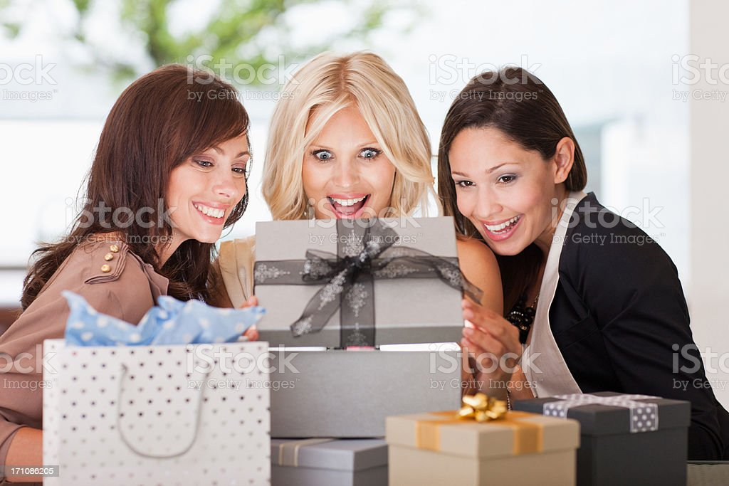 Friends watching woman open gift stock photo