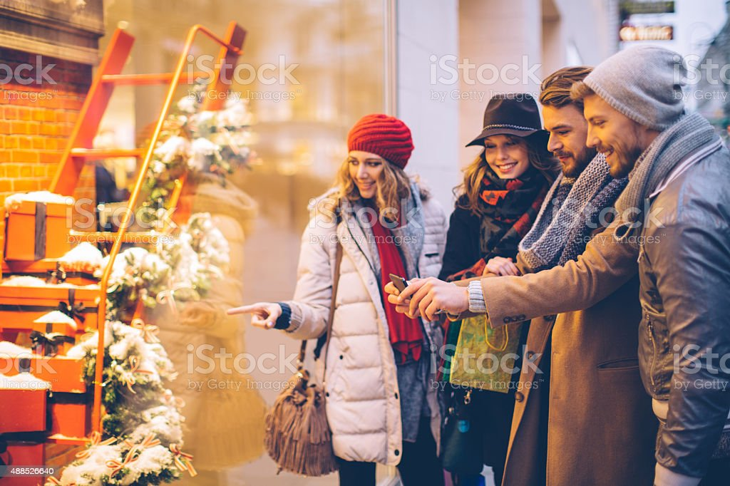 Friends window shopping outdoors in winter city street. stock photo