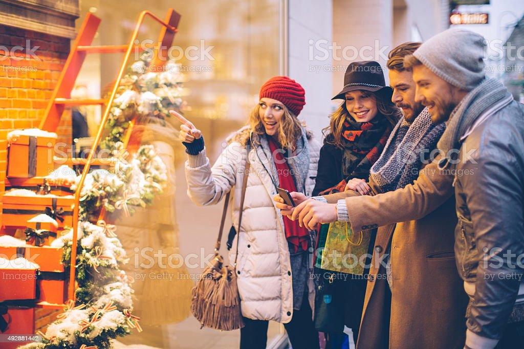 Friends window shopping outdoors in winter city street. stock photo