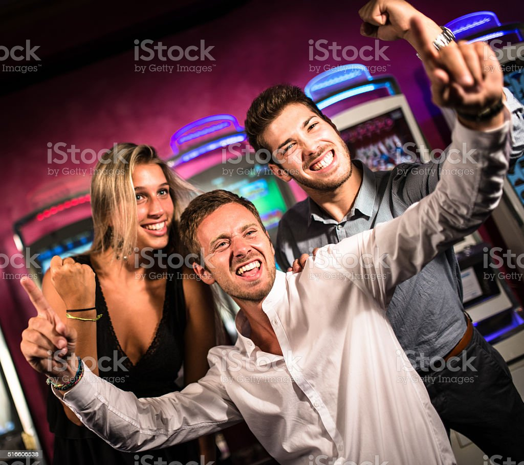 friends winning at slot machine stock photo