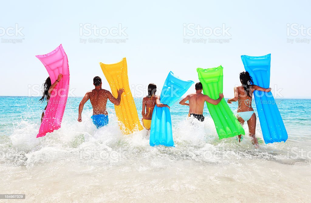 Friends with air mattresses running into surf royalty-free stock photo
