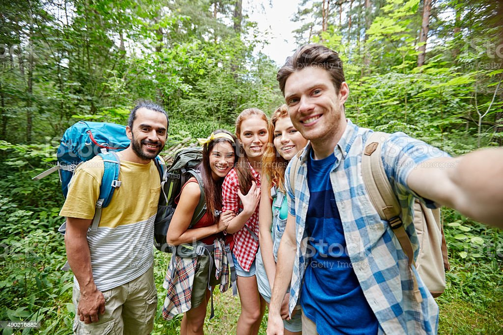 friends with backpack taking selfie in wood stock photo