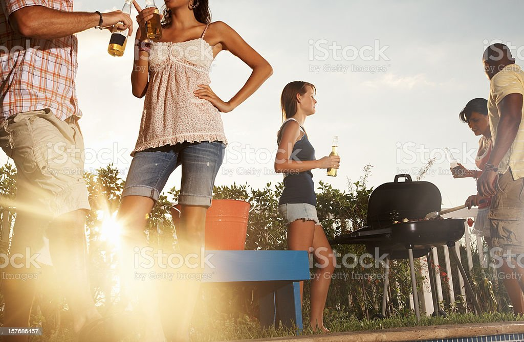Friends with barbecue and beer bottles enjoying their vacation stock photo