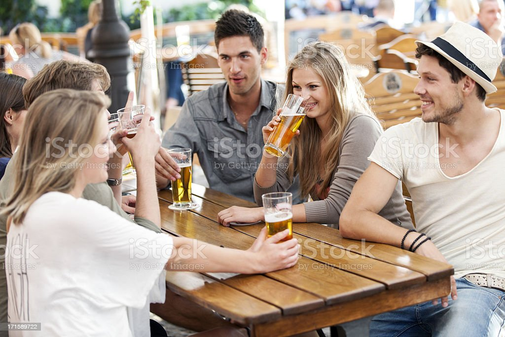 Friends with beer at a sidewalk cafe in Poland royalty-free stock photo